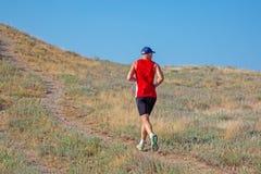 Tylni widok sportowy biegacza bieg na halnym śladzie na niebieskiego nieba tle obrazy stock
