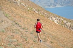 Tylni widok sportowy biegacza bieg na halnym śladzie na niebieskiego nieba tle obrazy royalty free