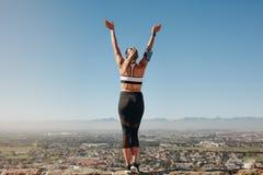 Tylni widok sprawności fizycznej kobiety pozycja na wzgórzu zdjęcia royalty free
