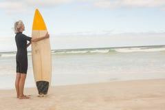 Tylni widok starszy kobiety mienia surfboard podczas gdy stojący na brzeg Zdjęcia Stock