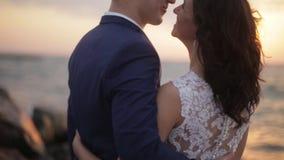Tylni widok szczęśliwa uśmiechnięta młoda para nowożeńcy tenderly ściska each inny patrzeje podczas jaskrawego i zbiory