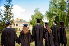 Tylni widok sześć pomyślnych międzynarodowych młodych absolwentów w bla Zdjęcia Royalty Free