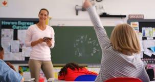 Tylni widok uczennicy dźwigania ręka w sali lekcyjnej 4k zdjęcie wideo
