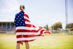 Tylni widok zawijający w flaga amerykańskiej żeńska atleta zdjęcia stock