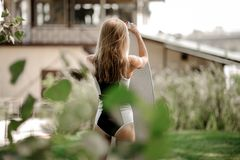 Tylni widoku blondynki dziewczyny pozycja z wakeboard obraz royalty free