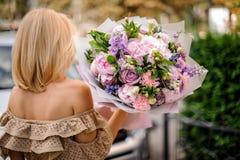 Tylni widoku blondynki kobieta trzyma bukiet czuły fiołkowy kwiat Fotografia Stock