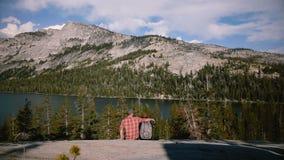 Tylni widoku mężczyzny spacery do siedzą kobietą i całują blisko zadziwiającego halnego jeziornego sceneria widoku przy Yosemite  zbiory