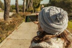 Tylni widoku mała dziewczynka bierze obrazki z smartphone Zdjęcia Stock