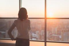 Tylni widoku portret przyglądający młodego pracownika mówienie używać telefon komórkowego out okno Kobieta ma biznesu wezwanie, r obrazy stock