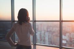 Tylni widoku portret przyglądający młodego pracownika mówienie używać telefon komórkowego out okno Kobieta ma biznesu wezwanie, r Zdjęcie Stock
