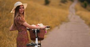Tylny plan: piękna blondynka w smokingowym i retro roweru odprowadzeniu na drodze w lata polu zdjęcie wideo