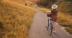 Tylny plan: Piękna blondynka w smokingowym i retro roweru odprowadzeniu na drodze w lata polu zbiory wideo