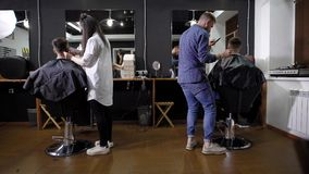 Tylny widok żeńscy i męscy hairstylists pracuje z klientów siedzieć zakrywam z tnącymi przylądkami w zakładzie fryzjerskim zbiory wideo