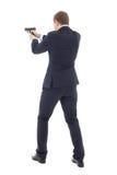 Tylny widok agenta specjalnego mężczyzna w garniturze pozuje z pistoletem Obrazy Royalty Free