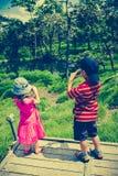Tylny widok azjatykci dzieci relaksuje outdoors w dniu, tr Obraz Stock