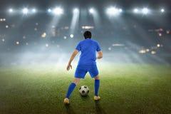Tylny widok azjatykci futbolista z piłką zdjęcia stock