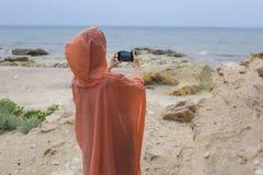 Tylny widok bierze fotografię zadziwiający denny wybrzeże młoda dziewczyna Zdjęcie Stock