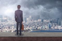 Tylny widok biznesmen patrzeje miasto z kopii przestrzenią na dachu obrazy stock