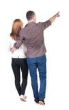 Tylny widok chodzący potomstwo pary wskazywać (mężczyzna i kobieta) Zdjęcia Stock