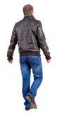 Tylny widok chodzić przystojnego mężczyzna w kurtce. Zdjęcia Royalty Free