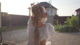 Tylny widok dosyć śliczna mała dziewczynka czyta książkowego obsiadanie na gankowych falowanie rękach w hełmofonach Dziecko zdjęcie wideo