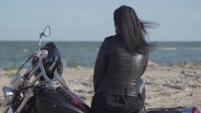 Tylny widok dosyć caucasian dziewczyny obsiadanie na motocyklu patrzeje daleko od na riverbank Hobby, podróżuje i zdjęcie wideo