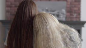 Tylny widok dwa dziewczyny z długim pięknym włosianym obsiadaniem blisko each inny w żywym pokoju Poj?cie przyja?? zdjęcie wideo