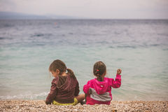 Tylny widok dwa małej dziewczynki siedzi blisko morza Fotografia Stock