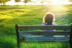Tylny widok dzieciaka obsiadanie na ławce przy zmierzchem w parku Zdjęcie Royalty Free