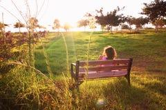 Tylny widok dzieciaka obsiadanie na ławce przy zmierzchem w parku Fotografia Royalty Free