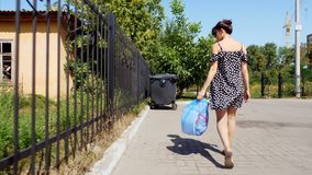 Tylny widok, dziewczyna niesie pakunek śmieci w jej rękach, rzuca out grat Lato gorący dzień ekologia rozdzielenie zbiory