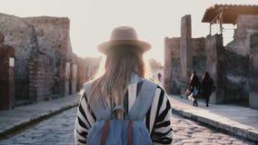 Tylny widok dziewczyna w kapeluszu z plecak pozycją po środku antycznej antykwarskiej ulicy w Pompeii, Włochy na słonecznym dniu zbiory wideo