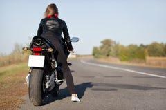 Tylny widok elegancki rowerzysta na motocyklu, pokrywy tęsk miejsce przeznaczenia, przejażdżki w wsi w otwartej drodze, cieszy si obraz royalty free