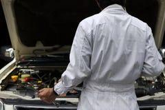 Tylny widok fachowy młody mechanika mężczyzna diagnozuje silnika przeciw samochodowi w otwartym kapiszonie przy naprawą w bielu m obraz stock