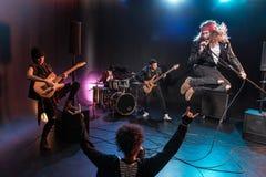 Tylny widok gestykuluje rock and roll ręki znaka i patrzeje zespołu młoda kobieta Zdjęcia Royalty Free