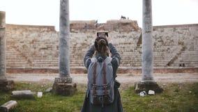 Tylny widok Kaukaska turystyczna dziewczyna z plecakiem bierze smartphone fotografię antyczni amfiteatrów filary w Ostia Włochy zbiory