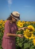 Tylny widok kobieta w kapeluszowym patrzeje słoneczniku Zdjęcia Royalty Free