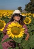 Tylny widok kobieta w kapeluszowym patrzeje słoneczniku Obraz Stock