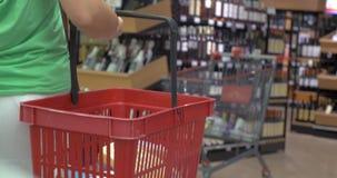 Tylny widok kobieta z koszem w sklepie