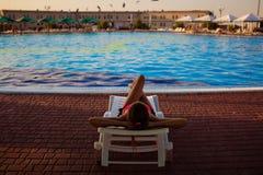 Tylny widok kobiety lying on the beach na lounger blisko basenu przy hotelem, poj?cia lata czas obraz royalty free