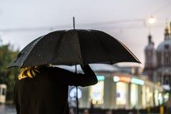 Tylny widok kobiety odprowadzenie podczas deszczu w mieście zdjęcie royalty free