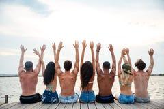 Tylny widok ludzie siedzi na molu z nastroszonymi rękami Obrazy Royalty Free