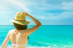 Tylny widok młody Azjatycki kobiety odzieży menchii bikini, słomiany kapelusz i okulary przeciwsłoneczni relaksuje, i cieszymy si obraz stock