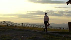 Tylny widok mężczyzna trzyma odprowadzenie wzdłuż ścieżki i bukiet podczas zmierzchu w kostiumu piękny widok natury zdjęcie wideo
