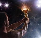 Tylny widok mężczyzna wojownik z trofeum filiżanką w rękach, zwycięstwa gestu Zdjęcia Stock