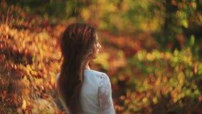 Tylny widok młoda długie włosy brunetka w białej sukni cieszy się naturę w jesień lesie zbiory