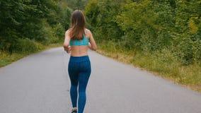Tylny widok młoda kobieta biegacza szkolenie w lato parku Sprawności fizycznej dziewczyny jogging plenerowy Ranku dzia?aj?cy poj? zbiory wideo