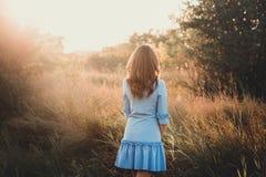 Tylny widok młoda kobieta ogląda zmierzch piękna dziewczyna na bardzo zielonej łące lub obraz stock