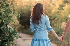 Tylny widok młoda kobieta ogląda zmierzch piękna dziewczyna na bardzo zielonej łące lub fotografia royalty free