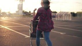 Tylny widok młoda kobieta pcha sklep spożywczy furę, podczas gdy jej przyjaciel siedzi inside podczas zmierzchu Obiektywu raca zbiory wideo